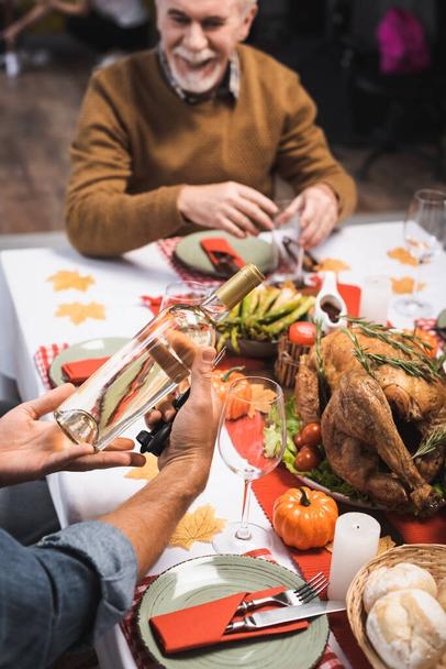 selective focus of man holding bottle of white wine while sitting at table served with thanksgiving dinner - Photo, Image