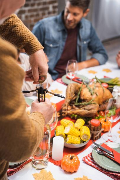 selective focus of senior man opening bottle of white wine during thanksgiving celebration with family - Photo, Image
