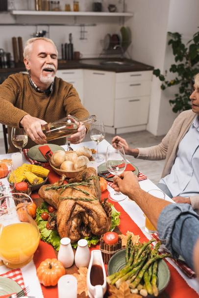selective focus of excited senior man pouring white wine during thanksgiving dinner with family - Photo, Image