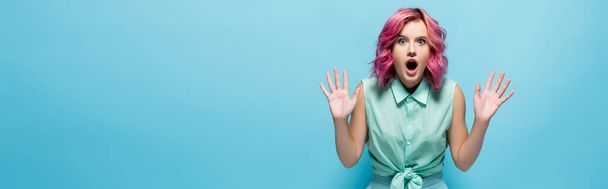 shocked young woman with pink hair and open mouth showing hands on blue background, panoramic shot - Photo, Image