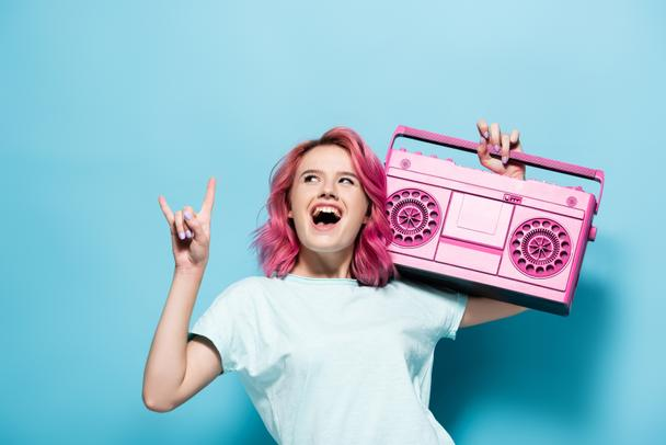 excited young woman with pink hair holding vintage tape recorder and showing rock sign on blue background - Photo, Image