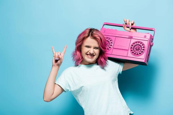young woman with pink hair holding vintage tape recorder and showing rock sign on blue background - Photo, Image