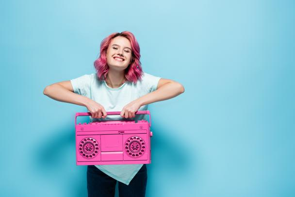 young woman with pink hair holding vintage tape recorder on blue background - Photo, Image