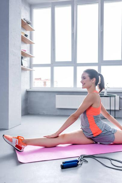 Partial view of sportswoman stretching on fitness mat near skipping rope at home - Photo, Image
