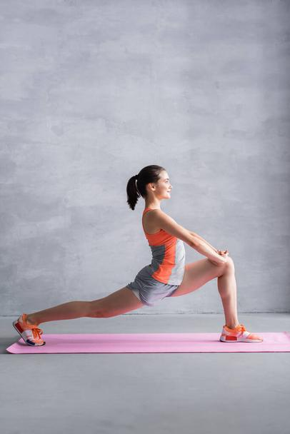 Side view of sportswoman doing lunge on fitness mat on grey background - Photo, Image