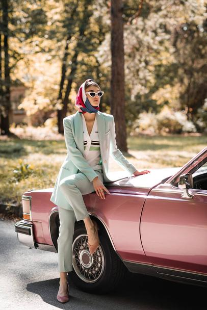 Fashionable woman in headscarf and sunglasses standing near retro auto on road  - Photo, Image