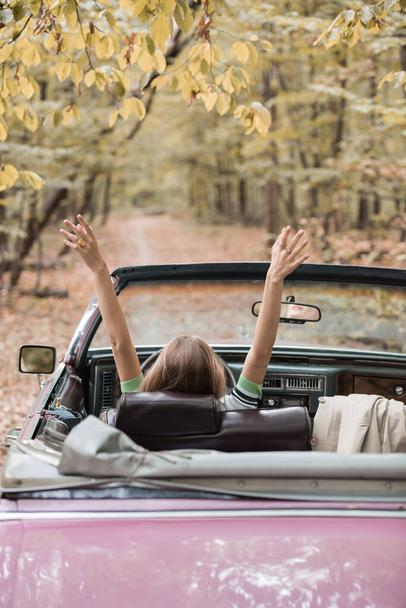 back view of young woman sitting in retro cabriolet in forest - Photo, Image
