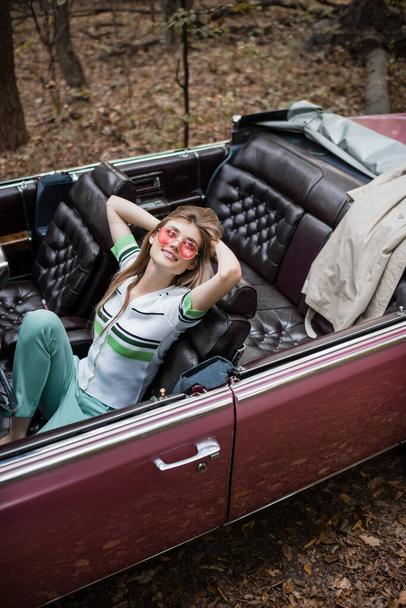 high angle view of joyful woman relaxing while sitting in vintage cabriolet with hands behind head - Photo, Image