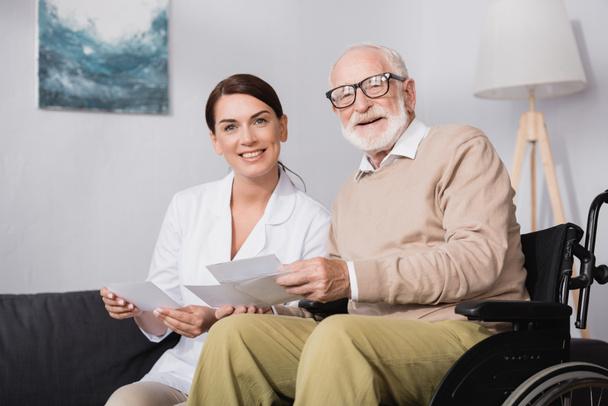 Lächelnder Sozialarbeiter und alter Mann, der in die Kamera schaut, während er Fotos hält - Foto, Bild