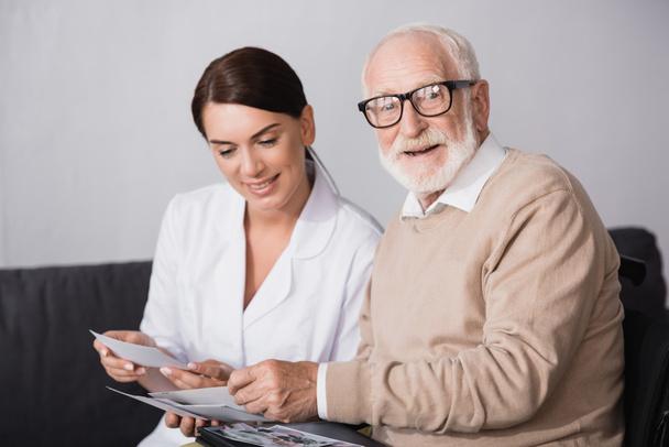 Älterer Mann blickt in Kamera, während Sozialarbeiter Familienfotos hochhält - Foto, Bild