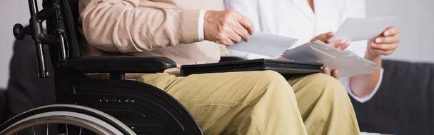 Ausgeschnittene Ansicht eines behinderten Mannes beim Betrachten von Fotos mit Sozialarbeiterin, Banner - Foto, Bild