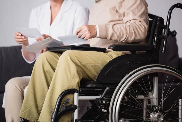 Ausgeschnittene Ansicht eines Sozialarbeiters, der behinderten Mann Familienfotos auf verschwommenem Hintergrund zeigt - Foto, Bild