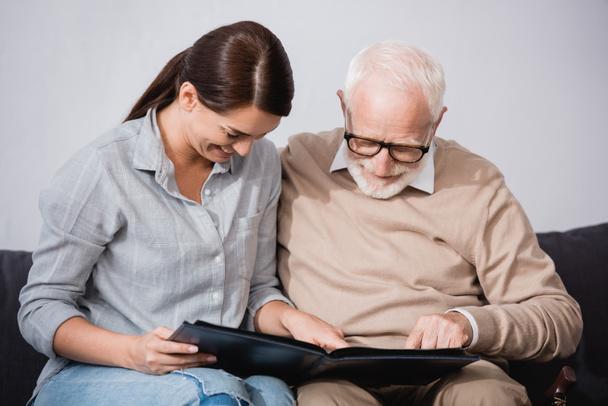 Brünette Frau mit älterem Vater schaut sich gemeinsam Fotoalbum an - Foto, Bild