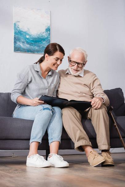 fröhlicher Vater und Tochter blättern im Fotoalbum, während sie zu Hause auf dem Sofa sitzen - Foto, Bild