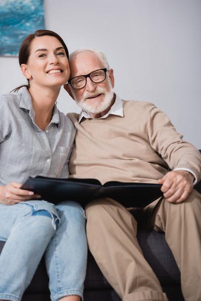 glücklicher Vater mit erwachsener Tochter, die in die Kamera lächelt, während sie ein Fotoalbum in der Hand hält - Foto, Bild