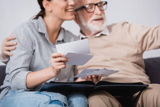 Lächelnde Frau beim Betrachten von Fotos, während sie in der Nähe ihres gealterten Vaters auf verschwommenem Hintergrund sitzt - Foto, Bild