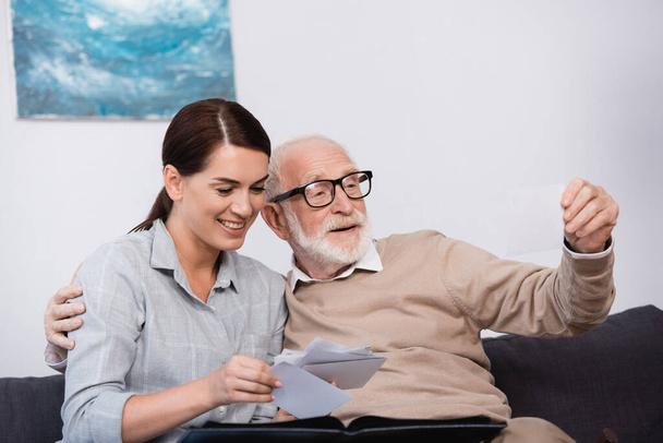 Lächelnde Frau mit älterem Vater beim gemeinsamen Betrachten von Familienfotos zu Hause - Foto, Bild