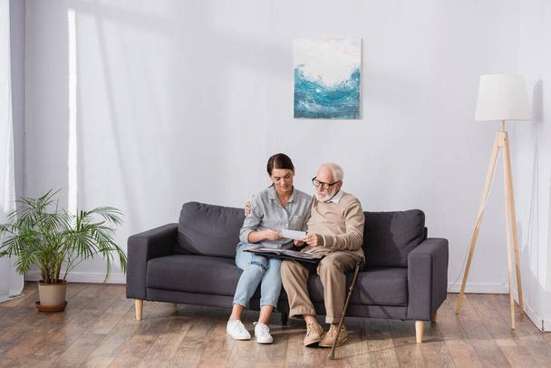 Älterer Vater mit erwachsener Tochter blättert im Fotoalbum, während er zu Hause auf dem Sofa sitzt - Foto, Bild