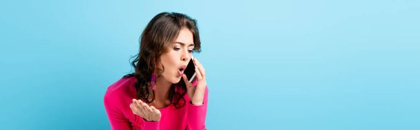horizontal crop of brunette woman screaming while talking on smartphone and gesturing on blue - Photo, Image