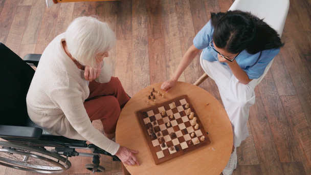 top view of elderly woman and nurse playing chess in nursing home - Footage, Video