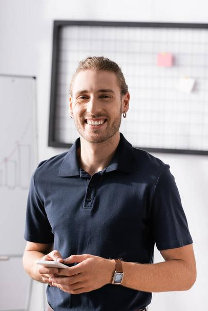 Happy office worker with smartphone laughing, while looking at camera at workplace on blurred background - Photo, Image