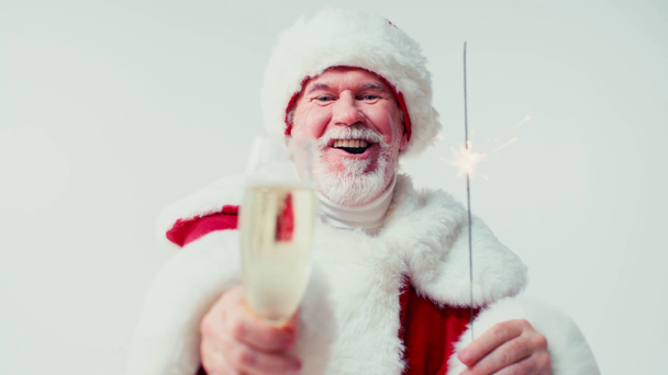 happy santa claus holding sparkler and glass of champagne isolated on white - Footage, Video