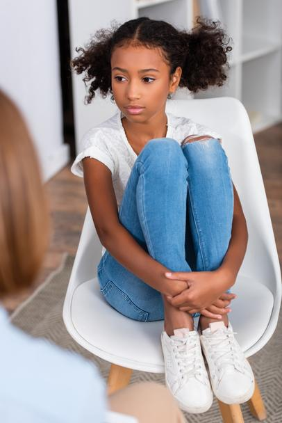 Serious african american girl hugging legs while sitting on chair during consultation with blurred psychologist on foreground - Photo, Image