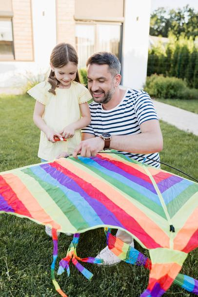 Full length of smiling daughter standing near father assembling kite on lawn with blurred house on background - Photo, Image