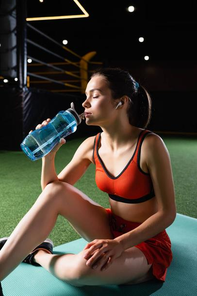 thirsty sportswoman with earphone drinking water from sports bottle while sitting on fitness mat with closed eyes - Photo, Image
