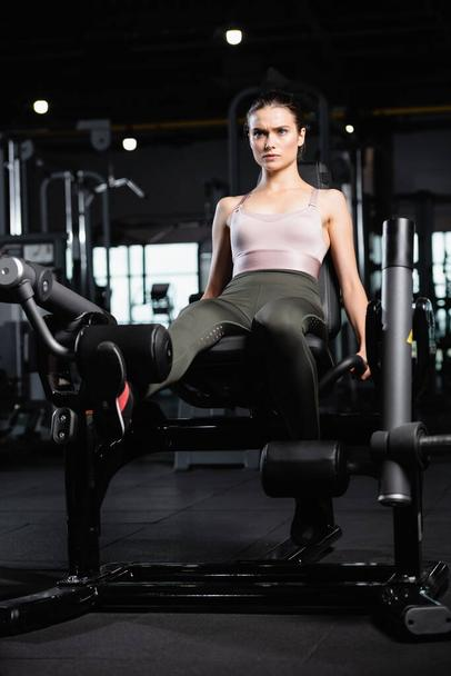 young sportswoman in leggings and bra doing leg extension exercise on training machine - Photo, Image
