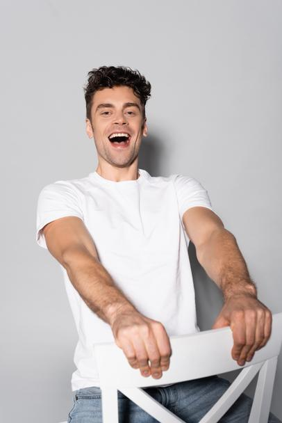 happy young man in white t-shirt on chair isolated on grey - Photo, Image