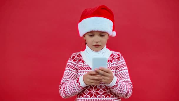 girl in santa hat and christmas sweater using smartphone isolated on red - Footage, Video