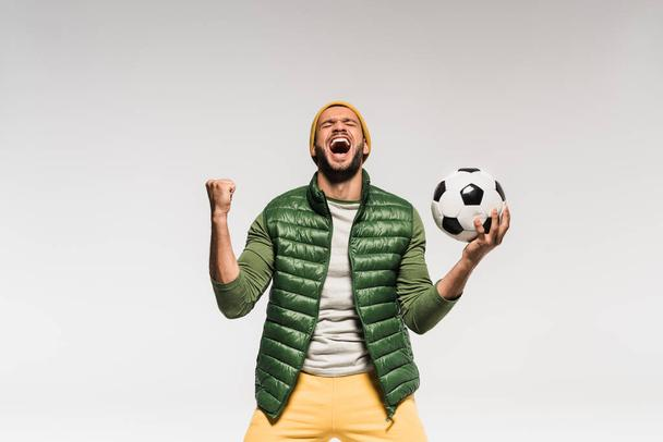 Excited sportsman holding football and showing yes gesture isolated on grey  - Photo, Image