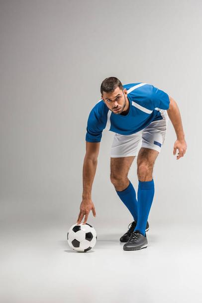 Confident sportsman looking at camera near football on grey background  - Photo, Image