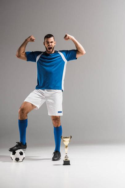 Excited sportsman showing yeah gesture near football and golden champions cup on grey background  - Photo, Image