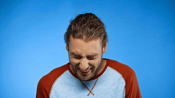 bearded young man with closed eyes laughing on blue  - Photo, Image