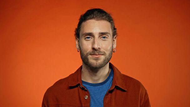 pleased bearded man looking at camera on orange background  - Photo, Image
