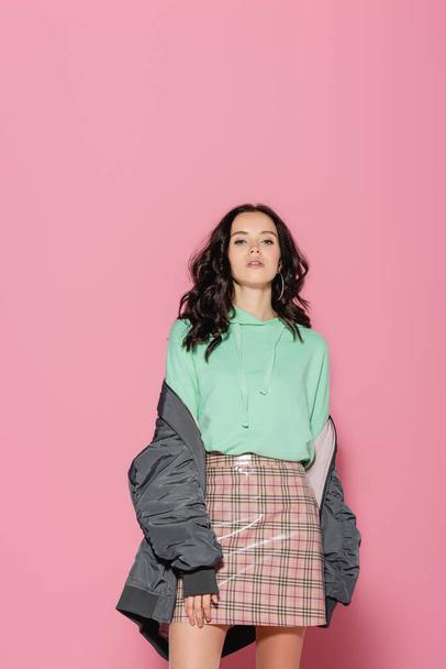 brunette young woman in casual winter outfit posing on pink background - Photo, Image