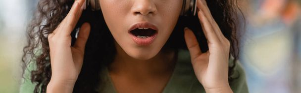 partial view of shocked african american woman listening podcast in cafe, banner - Photo, Image