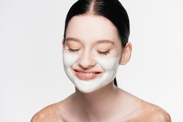smiling young beautiful woman with vitiligo and clay mask on face isolated on white - Photo, Image