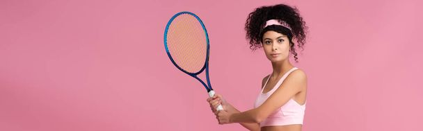 young curly sportswoman holding tennis racket while playing isolated on pink, banner - Photo, Image