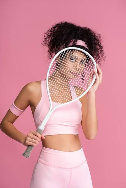 young sportive woman looking at camera through tennis racket isolated on pink  - Photo, Image