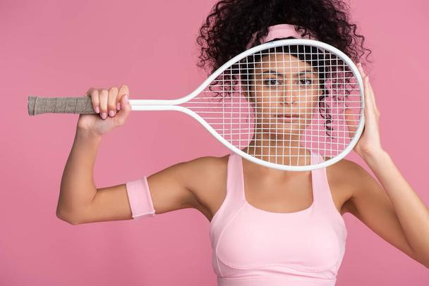 sportive young woman looking at camera through tennis racket isolated on pink  - Photo, Image