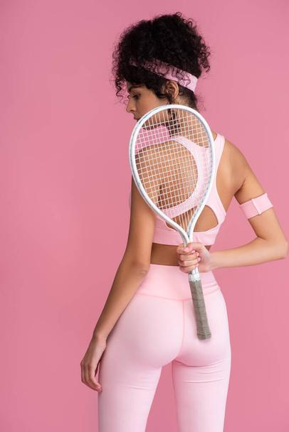 young sportive woman holding tennis racket behind back isolated on pink  - Photo, Image