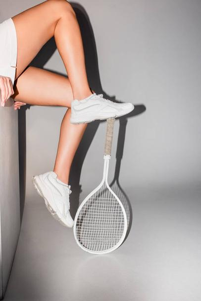 partial view of sportswoman in sneakers sitting on white cube near tennis racket on  grey - Photo, Image