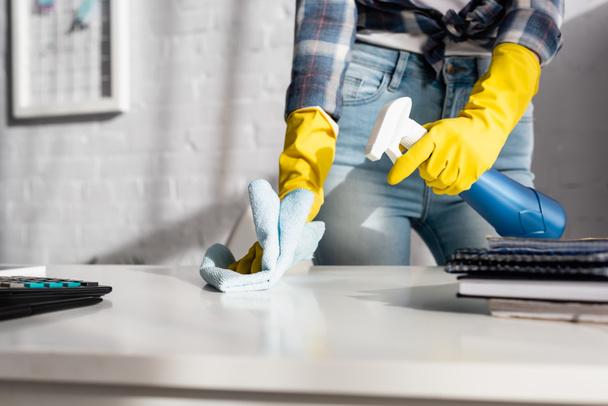 Розмитий передній план жінки в гумових рукавичках з ганчіркою і миючим засобом біля калькулятора.  - Фото, зображення