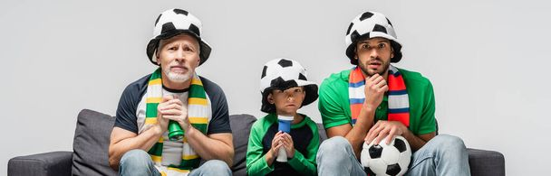 worried boy watching football match together with tense dad and grandfather isolated on grey, banner - Photo, Image