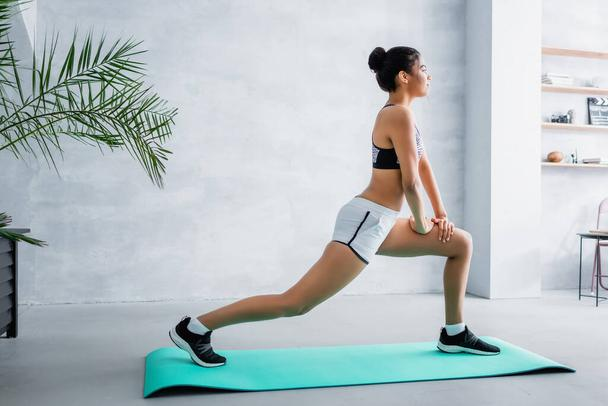 side view of sportive african american woman doing forward lunges exercise on fitness mat at home - Photo, Image