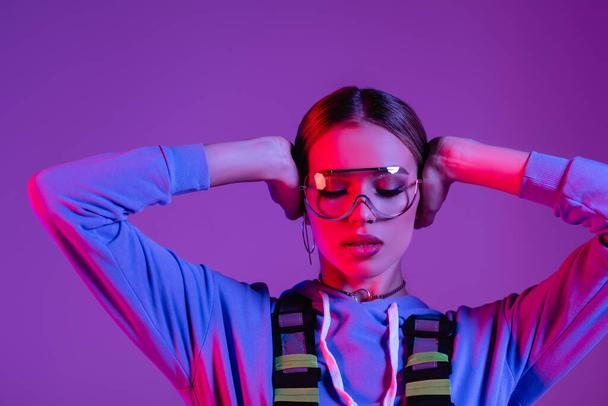young stylish woman in sunglasses and closed eyes isolated on purple  - Photo, Image
