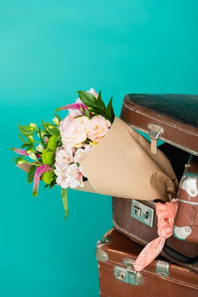 bouquet of fresh flowers and vintage suitcases isolated on turquoise - Photo, Image